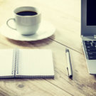 Laptop, coffee cup and notebook